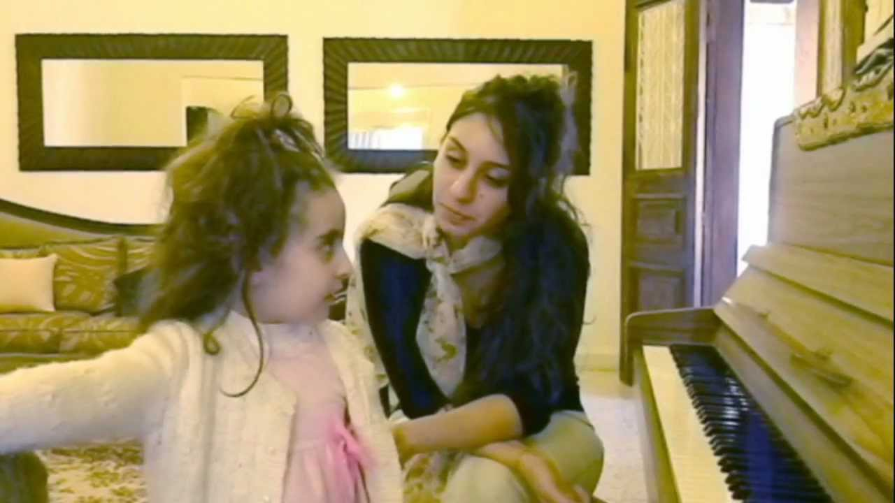 We see Hiba Najem stting next to a piano, and in front of her there's a little girl