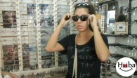 A picture of Hiba Najem in a glasses shop, trying on a pair of sunglasses.