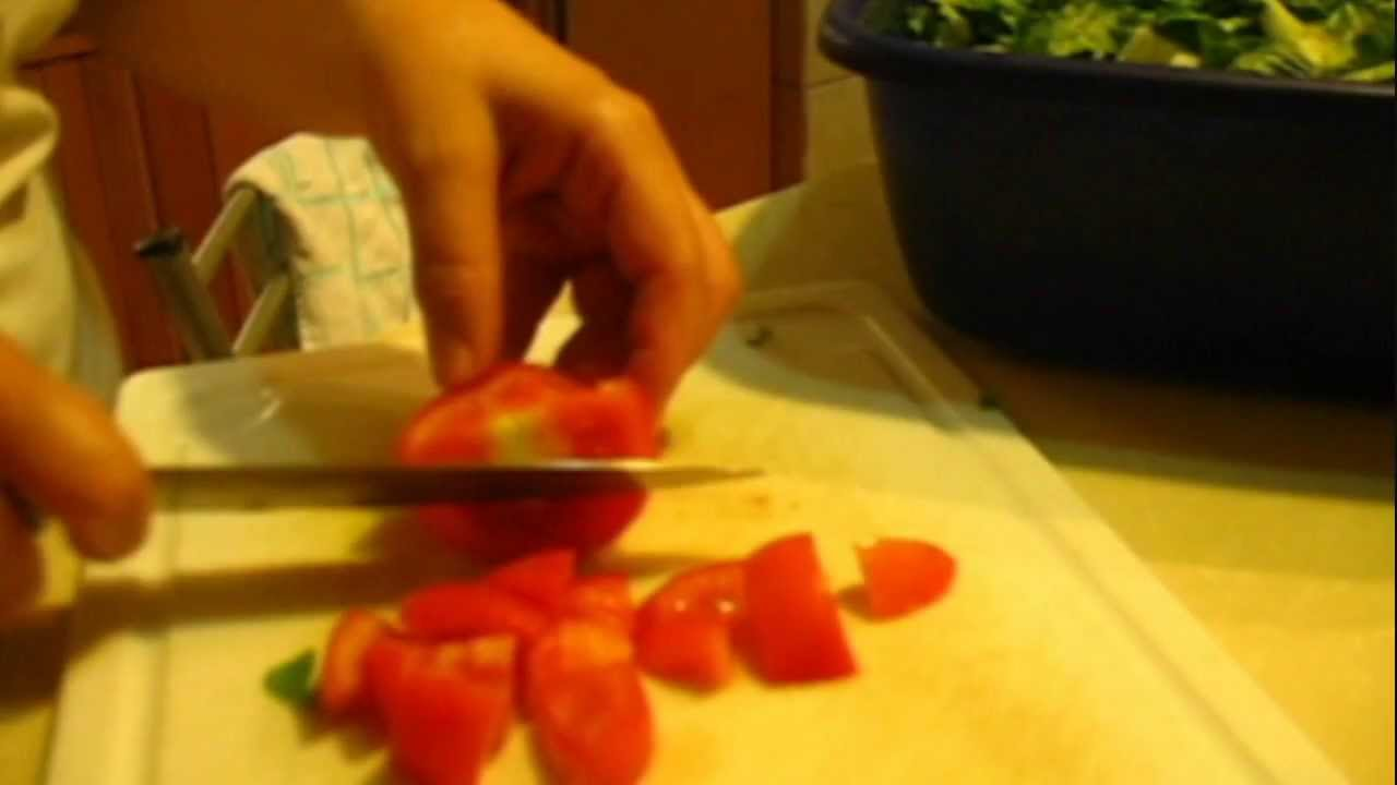 A close-up picture of a hand and knife cutting up a tomato.